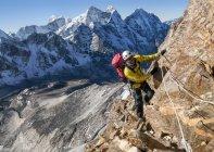 Nepal, Himalayas, Solo Khumbu, Ama Dablam, mountaineer climbing on rocks — Stock Photo