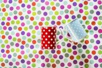 Tazas con puntos blancos sobre fondo colorido - foto de stock