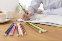 Male hand with colouring book and coloured pencils, close-up — Stock Photo