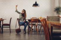 Молода жінка в ресторані закликають до офіціанта — стокове фото
