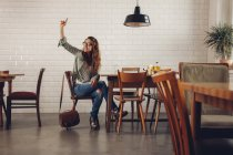 Young woman in restaurant calling for waiter — Stock Photo