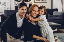 Счастливая семья с дочерью в гостиной — стоковое фото