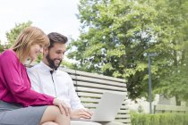 Smiling man with woman sitting on bench using laptop — Stock Photo