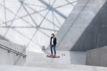 Businesswoman with pink skateboard in modern architecture — Stock Photo