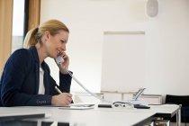 Улыбающаяся деловая женщина за столом офиса по телефону — стоковое фото