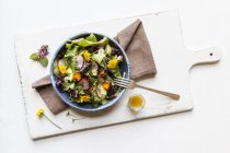 Bowl of mixed salad with edible flowers — Stock Photo