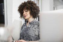 Жінка сидить за столом у кабінеті. — стокове фото