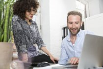 Smiling man and woman in office sharing laptop — Stock Photo