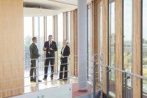 Três pessoas de negócios, comunicando-se em prédio de escritórios — Fotografia de Stock