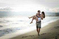Людина, несучи його подруга на пляжі — стокове фото