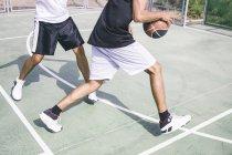 Обрезанный образ молодых спортсменов, играющих в баскетбол — стоковое фото