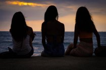 Mexico, Puerto Vallarta, three young women sitting at the Malecon boardwalk watching the sunset — Stock Photo