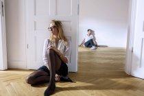 Женщина сидит на деревянном полу — стоковое фото
