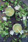 Bicchieri di frullato alle erbe selvatiche su superficie scura con ingredienti — Foto stock