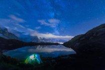 Vue panoramique de tente éclairée sur la rive du lac de nuit avec la voie lactée et Mont Blanc reflète dans le lac, le lac Cheserys, Mont Blanc, France — Photo de stock
