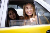 Giovani donne che guardano dal finestrino del taxi — Foto stock