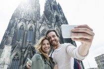 Germany, Cologne, portrait of young couple taking a selfie in front of Cologne Cathedral — Stock Photo
