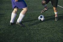 Gambe di calciatori sul terreno di gioco del calcio — Foto stock
