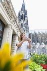 Jovem mulher de Alemanha, Colónia, tomando uma selfie com o smartphone na frente da Catedral de Colónia — Fotografia de Stock