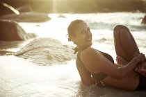 Сейшельские острова, улыбающаяся женщина, занимающаяся йогой у моря — стоковое фото