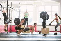 CrossFit athletes exercising together in gym — Stock Photo