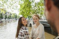 Niederlande, amsterdam, zwei lächelnde Frauen am Stadtkanal — Stockfoto