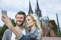Germany, Cologne, young couple taking a selfie with smartphone — Stock Photo