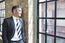 Mature businessman standing by window — Stock Photo