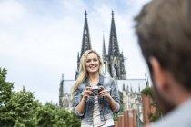 Німеччина, Кельн, портрет усміхається жінка з камерою, дивлячись на її бойфренд — стокове фото