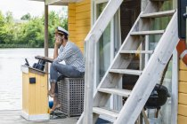 Man wearing captain's hat having a trip on a house boat — Stock Photo