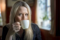 Portrait of blond woman drinking cup of coffee — Stock Photo
