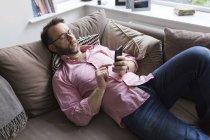 Зрілі чоловік лежить на дивані, перевірка повідомлень на смарт-телефон — стокове фото