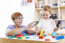 Ritratto di little boy and mother playing together mattoni da costruzione — Foto stock