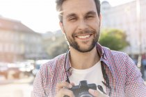 Portrait of smiling young man with camera — Stock Photo