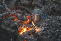 Bulgaria, Rhodope Mountains, camp fire with cup of water — Stock Photo