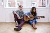 Pareja de jóvenes sentados en el piso con mujer tocando la guitarra - foto de stock