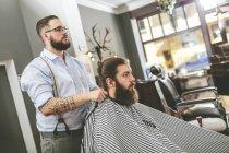 Barbiere legare mantello intorno cliente in barbiere — Foto stock
