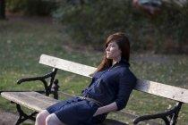 Portrait de femme assise sur un banc de parc — Photo de stock
