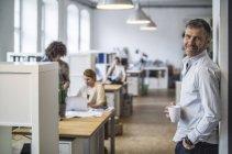 Hombre sonriente en la oficina con compañeros de fondo - foto de stock