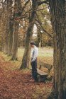 Young man standing in front of a bench in autumnal park — Stock Photo