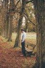 Молодой человек, стоящий перед скамейке в Осенний парк — стоковое фото