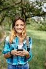 Ritratto di adolescente sorridente con smartphone e auricolari — Foto stock