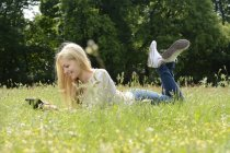 Young woman lying on a meadow using digital tablet — Stock Photo