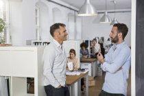 Sus colegas hablando en la oficina - foto de stock