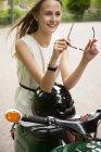Портрет улыбающейся девушки с мопедом и мотоциклетным шлемом — стоковое фото