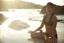 Сейшельские острова, женщина медитирует на берегу моря — стоковое фото