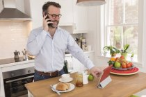 Man standing at breakfast table  in the kitchen telephoning with smartphone while using digital tablet — Stock Photo