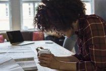 Жінка з мобільного телефону, сидячи в офісі — стокове фото