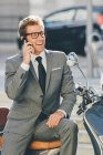 Businessman sitting on motor scooter — Stock Photo