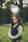 Portrait of little girl standing in an autumnal park — Stock Photo